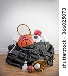 Small photo of sports equipment in a holdall sports bag on a gym floor. football, rugby, baseball, cricket, basketball, boxing, badminton, squash. Portrait with copy space.