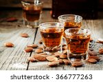 Small photo of Italian amaretto liqueur with dry almonds on the old wooden background, selective focus
