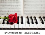 Red Rose On Piano Keys And...