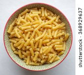 Small photo of Macaroni Uncooked Uncooked macaroni in a colorful ceramic bowl.