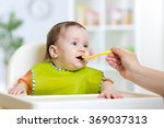mother feeding baby with spoon | Shutterstock . vector #369037313