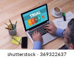 Small photo of Man working on laptop with TRIAL on a screen