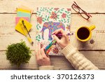 Small photo of Woman coloring an adult coloring book, new stress relieving trend, mindfulness concept, hand detail
