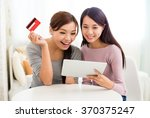 Two Woman Shopping Online With...