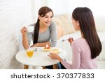 Two Young Woman Chatting At...