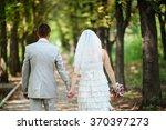 bride and groom walking away in ... | Shutterstock . vector #370397273