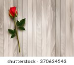 single red rose on a wooden...