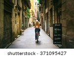 Small photo of Woman riding bicycle through old street of Barcelona