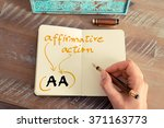 Small photo of Retro effect and toned image of a woman hand writing a note with a fountain pen on a notebook. Business acronym AA Affirmative Action with handwritten text