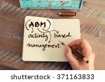 Small photo of Retro effect and toned image of a woman hand writing a note with a fountain pen on a notebook. Business acronym ABM Activity Based Management with handwritten text