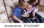 Small photo of Mother and two sons reading a tablet computer.