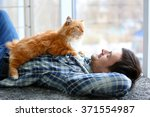 Stock photo young man with fluffy cat lying on a carpet 371554987