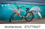 Small photo of Tofino, Vancouver Island, BC August 13, 2015 - A rental bike parked in front of a beautiful airbrushed mural of a blue whale & mermaid on the back of a store in Tofino, British Columbia, Canada.