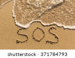 sos   word drawn on the sand... | Shutterstock . vector #371784793