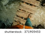 Stock photo man s legs on an old wooden bridge through the river 371905453