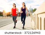 female joggers run on bridge... | Shutterstock . vector #372126943