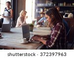 Small photo of Interior Of Coffee Shop With Customers Using Digital Devices
