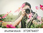 man photographer taking photos of flowers