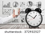 Small photo of hand holding a paper cup, the word 'pause' written over it. Black alarm clock to the right. White background. Concept of coffee break.