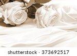 Stock photo  beautiful white roses on white silk as wedding background in sepia toned retro style 373692517