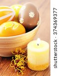 Small photo of Orange easter eggs in a cup with american witchhazel twig and candle.