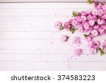 Stock photo background with bright pink flowers on white wooden planks selective focus place for text 374583223
