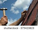 hand with a hammer to drive a... | Shutterstock . vector #375423823
