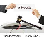 Small photo of Law book and wooden judges gavel on table in a courtroom or law enforcement office. Lawyer Hands holding business card with text Advocate