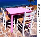 Small photo of Alfresco restaurant - traditional greek tavern with pink table and white chairs on the beach of Mediterranean sea,Crete, Greece. Selective focus, square toned image
