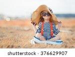 pretty little girl in a striped ... | Shutterstock . vector #376629907