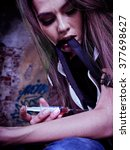 Small photo of Portrait of woman addicted to syringe on brick wall background.