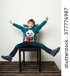 Small photo of Little funny boy is sitting on the chair, piddling, fooling