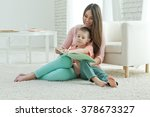 happy mother with baby reading... | Shutterstock . vector #378673327