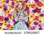 Stock photo beautiful young woman in nice blue dress posing on colorful wall of flowers fashion photo nice 378920857