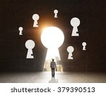 Small photo of A man with a case standing in front of a huge keyhole, many keyholes around it, city and sky seen through it. Black background. Back view. Concept of finding the way