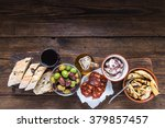 Small photo of Wooden board with tapas, olives and salami and olive oil, from above, copy space for text or advert.