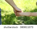 the parent holds the hand of a...   Shutterstock . vector #380811073