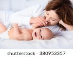 mother and child on a white bed.... | Shutterstock . vector #380953357