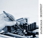 Small photo of Hand with tweezers above board with components. Repair of computers and modern technologies.
