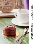 Small photo of Heart shaped mini mousse cakes covered with chocolate velour with cup of coffee on green table in cafe. Modern european cake for valentines. Shallow focus