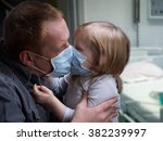 Small photo of Hospital ward. Father kissing daughter through medical mask. Little daughter. Father hugs daughter. Concept - disease, infection, childhood diseases, viruses