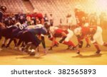 Small photo of American football game - out of focus background of the field in the sunset