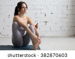 Small photo of Beautiful young woman working out in loft interior, doing Seated Hip Stretch, hip opener Eka Pada Agni Stambhasana, warming up on blue mat during practice, full length, copy space