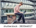 a man using laptop on the roof. | Shutterstock . vector #383366017