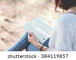 a young woman reading a book.... | Shutterstock . vector #384119857