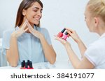 Small photo of Beautician showing nail polishes to enthusiastic female in nailcare salon
