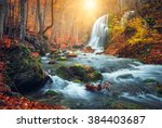 Stock photo beautiful waterfall at mountain river in colorful autumn forest with red and orange leaves at 384403687