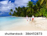 family with kid playing on beach | Shutterstock . vector #386452873