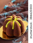 Small photo of Mini mousse cakes covered with chocolate velour and decorated with yellow glaze. Modern european cake on brown background. Shallow focus