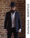 Small photo of Stylish young bearded man in gibus and sunglasses is looking at camera while standing against brick wall